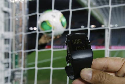 A FIFA official holds a wrist watch used in a goal-line technology system by GoalRef as he gives a demonstration in Yokohama